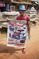 Nigeria. Enugu State. Enugu. Ogbete main market is the biggest commodity market. A man carries a poster with an advertisement for a chemical poison killing all rat, snake, scorpion, spider, cockroach, lizard and so on. Ogbete main market is the choice market for wholesale buyers and sellers. It is segmented into lines and lock-up shops. Each line is made up of various lock-up shops occupied by traders dealing on similar or related goods.  Residents of Enugu usually prefer going to Ogbete for major shopping, to buy things in bulk, to purchase quality and original goods, to have access to varieties, to buy new products and to buy goods at wholesale or company price. Enugu is the capital of Enugu State, located in southeastern Nigeria. 1.07.19 © 2019 Didier Ruef