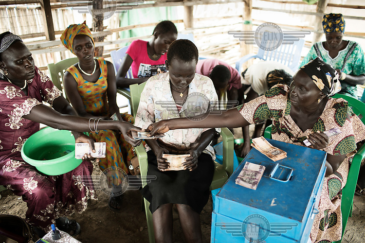 Women counting bank notes during a meeting of a village saving group (VSLA).