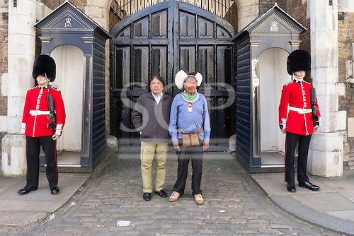 11 June 2014. Kayapo Chiefs Raoni Metuktire and Megaron Txucarramae during their visit to London. The chiefs stand in front of the gates to St James's Palace between two sentry boxes with a Coldstream Guardsman in full scarlet uniform and bearskin on each side.