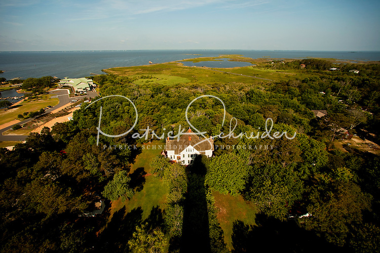 The view from Currituck Beach Lighthouse, one of the few North Carolina coastal lighthouses that visitors can climb to the top. Currituck Light is located on the Outer Banks in Corolla, North Carolina. With its red brick exterior, the lighthouse is  an example of Gothic Revival architecture. Located in the town of Corolla, the Currituck Beach Light was the last of four beacons placed at intervals from Cape Henry, Virginia to Cape Hatteras. Like other lighthouses on the North Carolina coast, the Corolla Lighthouse / Currituck Beach Lighthouse still aids ships in navigation. Charlotte NC photographer Patrick Schneider has extensive photo collections of the following lighthouses: Bodie Island Lighthouse, Bald Head Island Lighthouse, Cape Fear Lighthouse, Cape Hatteras Lighthouse, Cape Lookout Lighthouse, Currituck Beach Lighthouse, Diamond Shoal Lighthouse, Federal Point Lighthouse, Oak Island Lighthouse, and Ocracoke Lighthouse on Ocracoke Island.