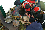 Elder Irwin Linklater shows three young Vuntut Gwitchin First Nation members how to skin caribou legs at a traditional winter camp near Old Crow, Yukon Territory, Canada.