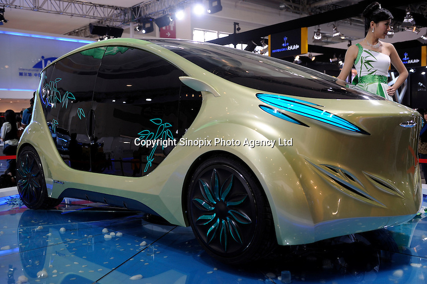 """A model poses next to an IAT (International Application Technology) """"Zu"""" electric concept car, designed by IAT (China) Automobile Technology, at the Beijing Auto Show in Beijing, China. The car show has attracted all the world's major auto markers. China's vehicle sales have breached the 10-million barrier for the first time ever, with 10.9 million automobiles sold last year. .24 Apr 2010"""
