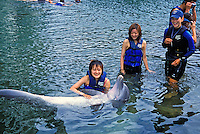 Tourists interact and pose for pictures with an Atlantic Bottlenose Dolphin in the lagoons of the Kahala Mandarin Hotel and Resort.  Oahu. Dolphins are trained by staff from Sea Life Park.