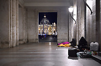 Homeless people sleeping near St. Peter's Square, with St. Peter's Basilica with Christmas tree in the background at the Vatican.14 december 2020