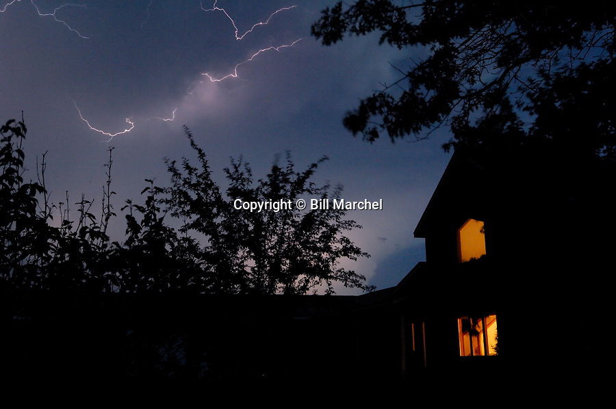 00715-003.18 Lightning:  Lightning and ominous clouds with trees and home in foreground.  Storm, rain, backyard.
