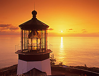 Cape Meares Lighthouse with sunset reflected on water. Oregon.