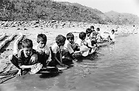 India, Narmada River, Narmada dams and protest movement of NBA Narmada Bachao Andolan, movement to save the Narmada river, and affected Adivasi in their villages, village Nimghavan, Adivasi children washing their lunch meal plates at Narmada river