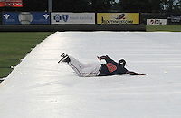 Infielder William Beckwith (48) of the Rome Braves slides across the tarp to catch a ball during a lengthy rain delay before a game against the Greenville Drive on July 5, 2012, at Fluor Field at the West End in Greenville, South Carolina. The game eventually was postponed due to rain. (Tom Priddy/Four Seam Images)