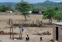 Zambia, Sinazese, village Nkandabbwe, chinese Collum coal mine, villager in resettlement / SAMBIA, Dorfbewohner mußten der chinesischen Collum Kohlemine weichen und wurden umgesiedelt, Hintergrund LKW holen Kohle von der Kohlemine