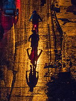 Push Bike riders on the road during the Monsoon season in Manila, dramatic light and a heavy rain shower at night viewed from above made for some abstract images.