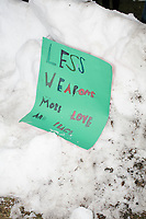 "A sign reading ""Less weapons / More love and peace"" lays in a snow bank as people gather during the March For Our Lives protest and demonstration in Boston Common in Boston, Massachusetts, USA, on Sat., March 24, 2018. The march was held in response to recent school gun violence."
