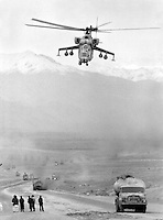 """A Soviet Mi-24 """"Hind"""" attack helicopter escorts a fuel convoy on its way to the Afghan capital Kabul on Sunday, February 5, 1989. Under siege for several years, the regime in Kabul depends heavily on Soviet military support."""