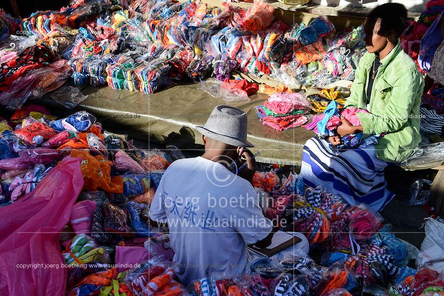 MADAGASCAR, Mananjary, market, street vendoor sells chinese clothes / MADAGASKAR Mananjary, Markt, Stand verkauft chinesische Textilien