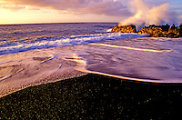 Waves crash against the lava rocks at a remote black sand beach on the Big Island of Hawaii.