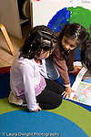 Education preschoool children ages 3-5 two girls sitting and talking looking at picture book vertical
