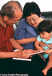 10 month old baby boy sitting with grandparents looking at board book vertical
