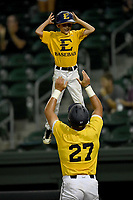 Right fielder Aaron Maher (27) of East Tennessee State tosses 10-year-old Gehrig Skole, son of head coach Tony Skole, into the air after scoring a run in a game against Furman at the Southern Conference Baseball Championship on Saturday, May 27, 2017, at Fluor Field at the West End in Greenville, South Carolina. Furman won, 8-6. (Tom Priddy/Four Seam Images)