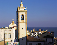 Church-steeple against a background of blue sky and sea, in the old town of Albufeira, Algarve, Portuga