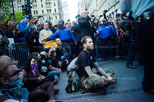 New York, New York.May 1, 2012..Demonstrators sit down on the streets at the intersection of Wall Street and Broadway. One was arrested...Approximately 20,000 people gathered to celebrate May Day, the International Labor Day, and to protest economic inequality as part of the Occupy Wall Street movement.
