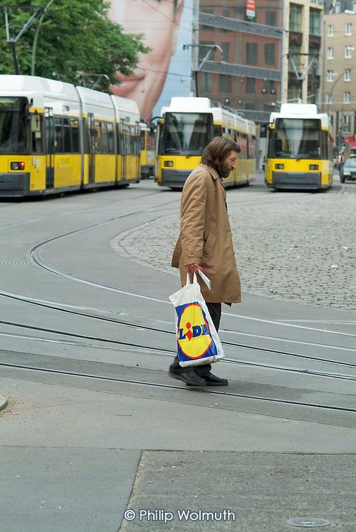 A homeless Berlin man carries a Lidl bag in Hackescher Markt