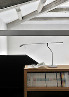 A detail of a home office room with a painted beamed ceiling. A sleek lamp stands on top of a wooden book case.