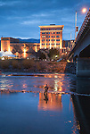 Missoula Montana downtown area viewed from across the Clark Fork River. Lights of the downtown area at dusk. The Wilma building and the Higgins Avenue bridge and a fisherman in the river.