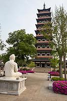 Yangzhou, Jiangsu, China.  Statue of the Buddha in Daming Temple Grounds.  Daming Pagoda in Background.