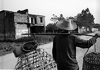 A farmer passes a house in Bobai county outside Yingqiao that has been smashed up. The house and the surrounding area have slogans from the One Child Policy, 'fewer babies better life' and ' a sensible birth policy is essential for development'.