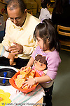Education Preschool 3-4 year olds male teacher working with girl in pretend play area talking vertical