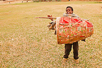 Beside the timket celebration a boy carryng a big drum is dancyng  with pleasure