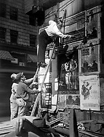 Second Liberty Loan, Oct. 1917.  Fattie Arbuckle, the movie star, putting up a Liberty Loan poster at Times Square, New York.  Paul Thompson. (War Dept.)<br /> Exact Date Shot Unknown<br /> NARA FILE #:  165-WW-232B-13<br /> WAR & CONFLICT BOOK #:  519