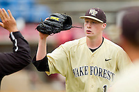 Wake Forest Demon Deacons relief pitcher John McLeod #17 high fives a teammate after getting out of an inning against the Virginia Tech Hokies at Wake Forest Baseball Park on April 21, 2012 in Winston-Salem, North Carolina.  The Demon Deacons defeated the Hokies 8-6.  (Brian Westerholt/Four Seam Images)