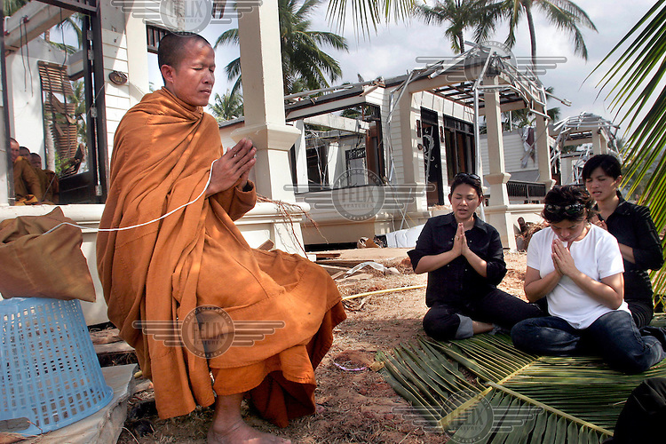 A Buddhist monk performs a ceremony for the victims of the tsunami which struck South Asia on 26/12/2004, in particular the grandson of the King of Thailand who stayed in the bungalow in the background.An underwater earthquake measuring 9 on the Richter scale triggered a series of tidal waves which caused devastation when they struck dry land. 12 countries were affected by the tsunami, with a combined death toll of over 150,000. © Fredrik Naumann