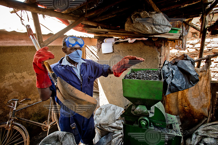 In a backyard workshop, a member of the Lulana Communal Environmentalist group making briquettes for use as cooking fuel, an alternative to charcoal or wood, shreds the raw material, recycled or waste cardboard. LCE sells its briquettes to individuals and restaurants.