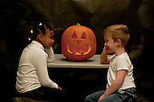 MR / Schenectady, NY. Two children look at each other from opposite sides of a lit jack-o-lantern carved from pumpkin in a dark room. Girl left: 6, African-American. Boy right: 6. MR: Joh18, Lus1. ID: AK-ICP. © Ellen B. Senisi