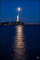 The Statue of Liberty with rising moon and moonlight reflection.