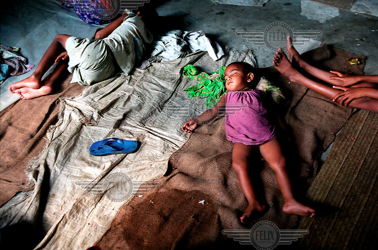 Children sleep on a classroom floor. Many families take shelter in local schools during flooding. Monsoon rains caused flooding in 40 of Bangladesh's 64 districts, displacing up to 30 million people and killing several hundred.