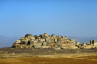 The village of Hagjar Sa sits in the distance, on top of a rocky hill, under a dark and cloudless sky. Cultivated fields are in the forefront. cityscapes, dwellings, buildings. Hagjar Sa, Yemen.