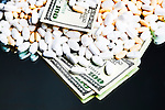 Drugs and Money.  Legal prescription drugs represented with U.S. currency. Conceptual image representing drug culture, medical, insurance, dichotomy, and more. Available exclusively through www.spacesimages.com