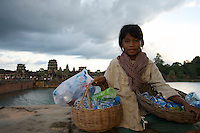 A young khmer girl collecting plastic bottles that are left by visiting Tourist at Angkor Wat, Cambodia, Siem Reap.