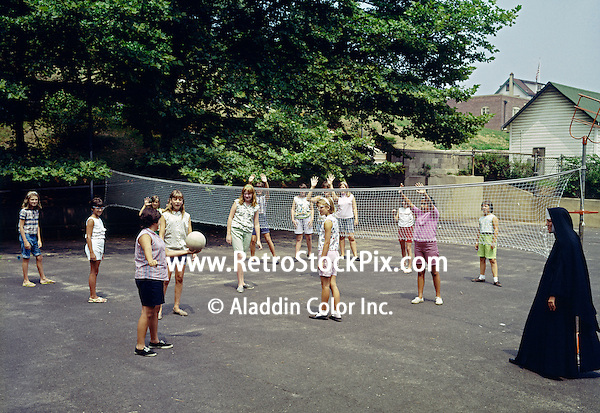 Saint John Villa Academy, NY. Nun teaching young girls how to play volleyball.
