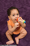 sitting 5 month old baby girl full length biting toy portrait looking at camera/viewer