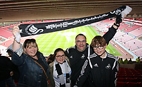 A young family of Swansea supporters hold a scarf high prior to the Premier League match between Sunderland and Swansea City at the Stadium of Light, Sunderland, England, UK. Saturday 13 May 2017
