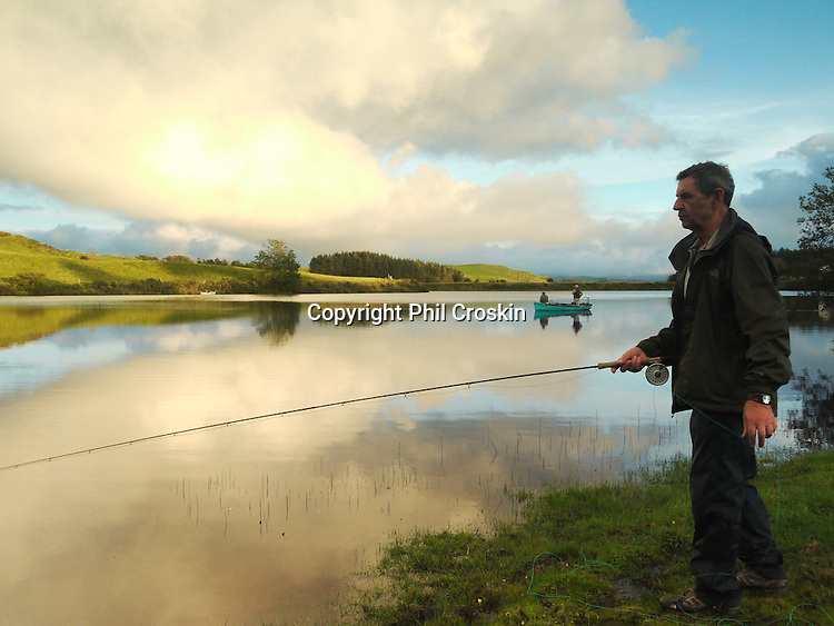This photo was taken at Llyn Frongoch in close proximity to the village of Trisant, close to the Aberystwyth to Devil's Bridge road. Frongoch is a fly only lake and is regularly stocked with both brown and rainbow trout. The quality of fish is excellent and boats are available. At Frongoch, Aberystwyth Angling Association have two caravans for hire for visitors wishing to stay in the area and take advantage of the fishing in this small but delightfully situated lake. Admist wonderful upland scenery, close to the Rheidol and Ystwyth valleys, and just twelve miles from the coast at Aberystwyth they represent excellent value for anyone wishing to combine angling with a family holiday. Stock Photo by Phil Croskin.