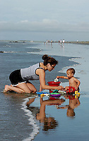 A toddler and young woman sit along the shore of the ocean.