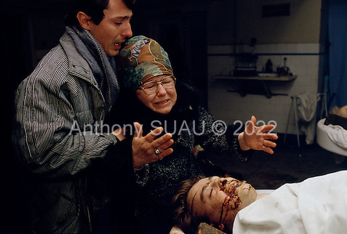 """Bucharest, Romania<br /> December 24, 1989<br /> <br /> A mother in the city morgue grieves for her son who was killed in the uprising overthrowing former leader Nicolae Ceausescu.<br /> <br /> The week-long series of violence that overthrew the Communist regime of Nicolae Ceausescu, ended in a trial and execution of Ceausescu and his wife Elena by firing squad. Romania was the only Eastern Bloc country to violently overthrow its Communist regime or to execute its leaders.<br /> <br /> The Romanian populace was dissatisfied with the Communist regime and leader Ceausescu's economic and development policies were blamed for the country's shortages and widespread poverty. The powerful secret police (Securitate) controlled what was essentially a police state. Ceausescu was not pro-Soviet but """"independent"""" on foreign policy. He imitated the hard-line, megalomania, and personality cults of communist leaders like North Korea's Kim Il Sung."""
