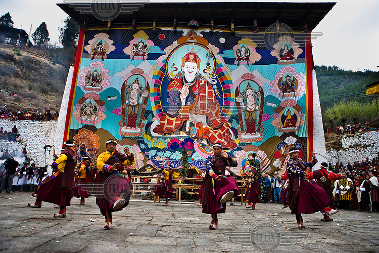 Traditional Bhutanese dancers dance in front of an ancient and giant thangka, a silk painting with embroidery, that is unveiled during a festival in Paro Dzong in Paro, Bhutan.
