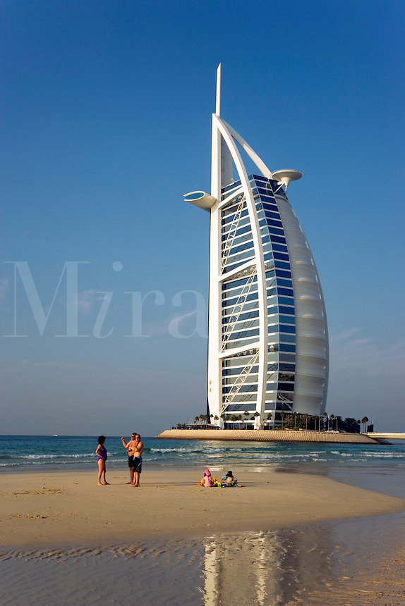 Dubai.  Family group and Burj al Arab Hotel, architect W.S. Atkins, an icon of Dubai built in the shape of the sail of a dhow, stands on an island off Jumeirah Beach.  .