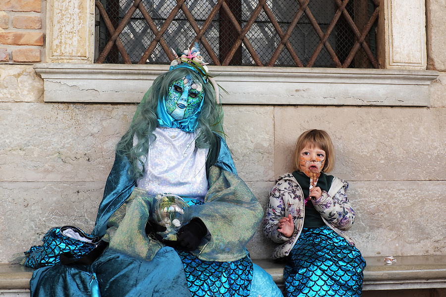 Mother and daughter dressed in traditional mask and costume for Venice Carnival exhausted and sitting on bench at Doge's Palace, girl eating ice cream cone, Piazza San Marco, Venice, Veneto, Italy