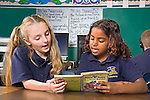 Two girls,Caucasian and African American,second graders read at their desk.together with classroom rules posted in the schoolroom in New Orleans